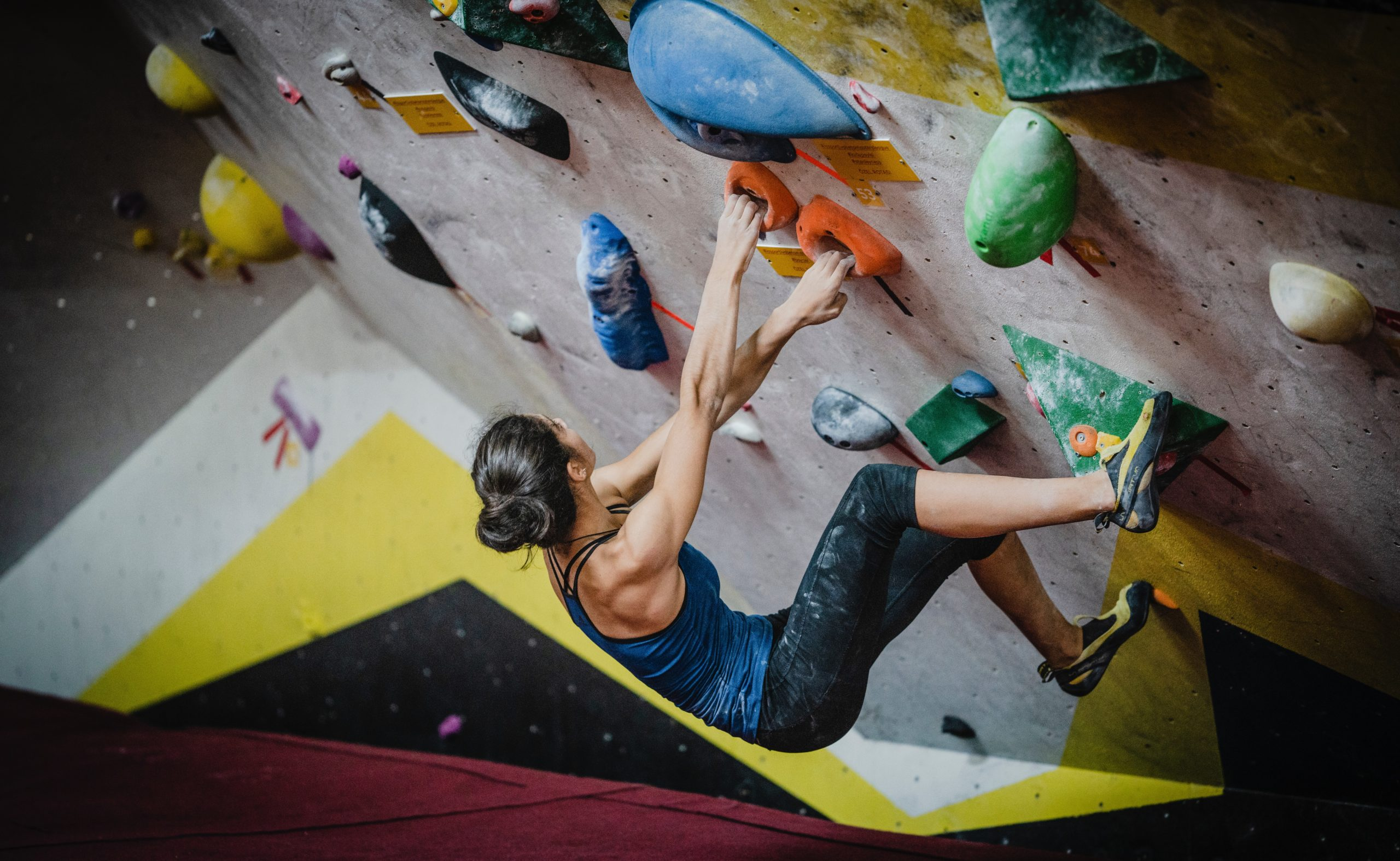 A woman bouldering inside at a gym