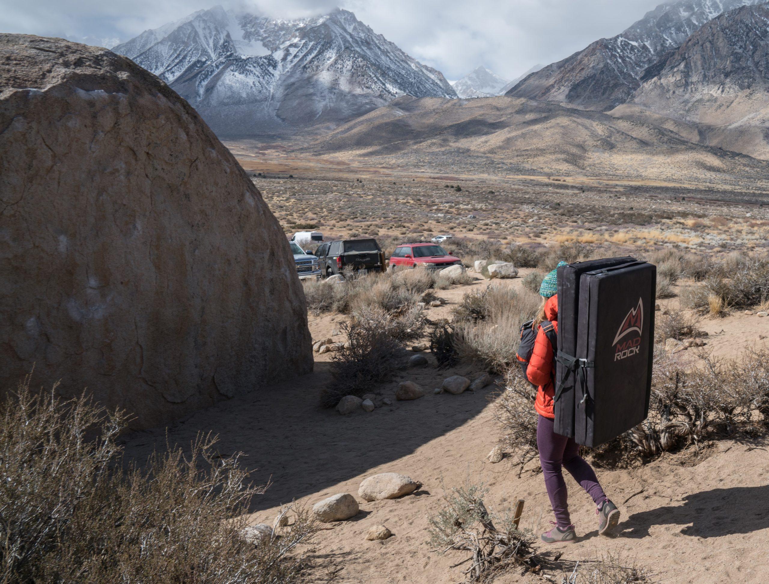 A woman walking towards a boulder problem